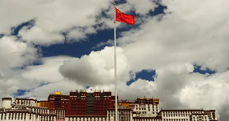 sziámi : china national flag in potala square,white clouds in blue sky,tibet. Stock mozgókép