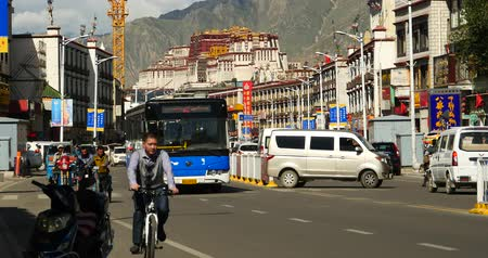 пагода : busy traffic & crowd in lasa business street,far away lhasa building & potala.