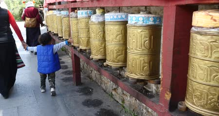 hacı : tibetan person turn spinning buddhist prayer wheels,lhasa.lhasa Tibetans wearing traditional clothing. Stok Video