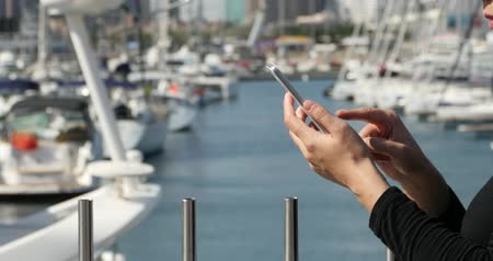 portátil : A girl using a smartphone at seaside,yacht & sailing in the harbour.