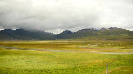 запад : white puffy clouds mass rolling over Tibet mountain top & valley,river flowing through the prairie,roof of the World.