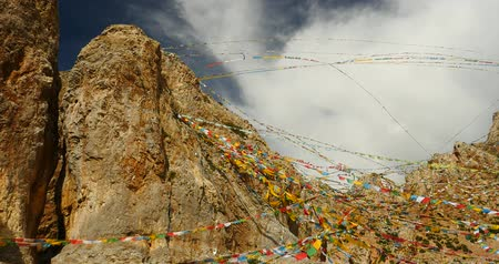 inculto : Prayer flags at the lake namtso in tibet,ancient holy monk meditation in cave,ZhaXi Peninsula,tibet mansarovar,Tibets second largest lake,is the third largest saltwater lake in China.Danggula(Tanggula) Mountains in xizang Plateau,roof of the World.