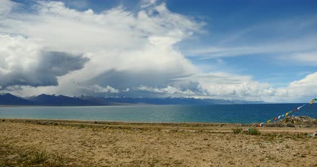 sefer : huge clouds mass rolling over lake namtso & Tanggula snow mountain peak,tibet mansarovar,pray flag in wind,Tibets second largest lake,is the third largest saltwater lake in China.Danggula(Tanggula) Mountains in xizang Plateau,roof of the World. Stok Video