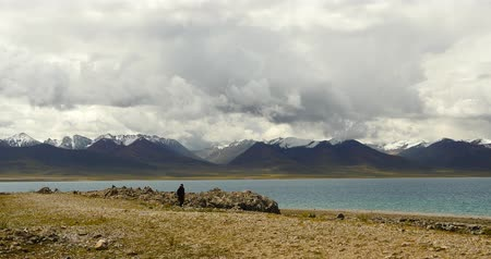 parke taşı : Tibetans walking the pilgrim at the lake namtso in tibet,Prayer flags in the wind,ancient holy monk meditation in cave,ZhaXi Peninsula,tibet mansarovar,Tibets second largest lake,is the third largest saltwater lake in China.Danggula(Tanggula) Mountains i Stok Video