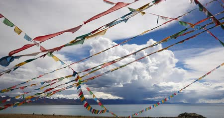 lucky charm : huge clouds mass rolling over lake namtso & Tanggula snow mountain peak,tibet mansarovar,pray flag in wind,Tibets second largest lake,is the third largest saltwater lake in China.Danggula(Tanggula) Mountains in xizang Plateau,roof of the World. Stock Footage