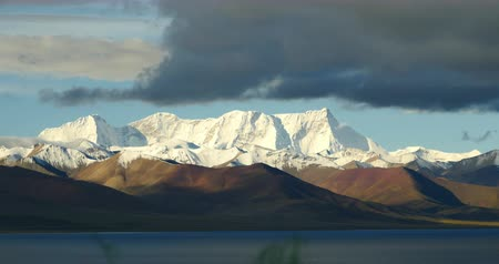 soft earth : huge clouds mass rolling over lake namtso & Tanggula snow mountain peak,tibet mansarovar,Tibets second largest lake,is the third largest saltwater lake in China.Danggula(Tanggula) Mountains in xizang Plateau,roof of the World.