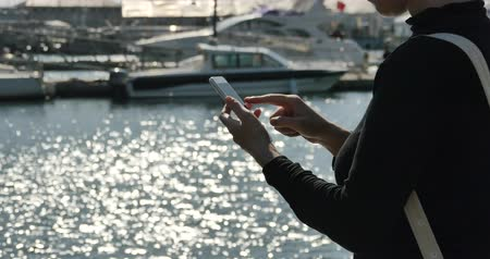 odeslat : A girl using a smartphone at seaside,yacht & sailing in the harbour,Sparkling water surface.