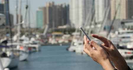 fejlesztése : A girl using a smartphone at seaside,yacht & sailing in the harbour.