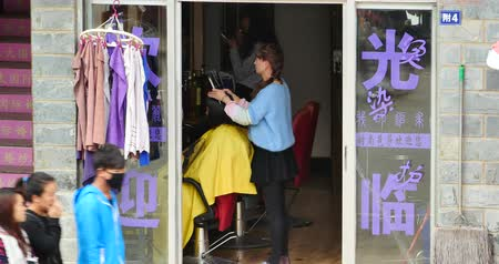 kuaför : young girl gets a haircut in tonsorial,shangri-la yunnan,china. Stok Video