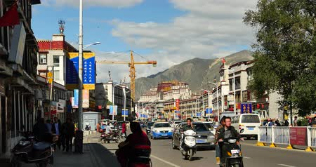 невозделанный : busy traffic & crowd in lasa business street,far away lhasa building & potala.
