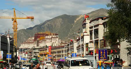 поток : busy traffic & crowd in lasa business street,far away lhasa building & potala.
