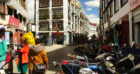wall building feature : tibetan & tourist walking on famous barkhor street in lhasa,tibet,butter store.