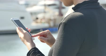odeslat : A girl using a smartphone at seaside,yacht & sailing in the harbour.