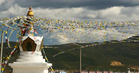 tanítvány : buddhist white stupa and flying prayer flags with clouds background,shangrila yunnan,china.