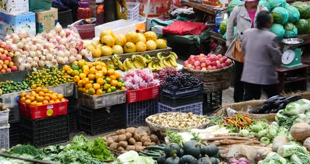 bakkal : large outdoor fruits trade market in Shangri-La,china,minority women,variety of fruits in basket. Stok Video