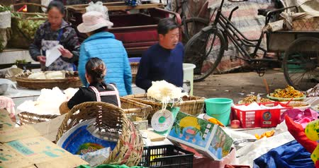 shangri la : large outdoor fruits trade market in Shangri-La,china,minority women,variety of fruits in basket. Stock Footage
