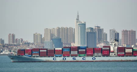 áruk : Cargo Container Ships Through The Qing Dao Harbor,modern urban building,china. Stock mozgókép