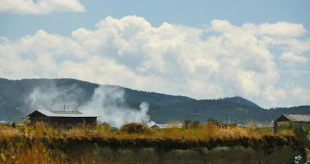 shangri la : burn smoke and tibetan-houses,clouds mass rolling over mountains in Shangri-La yunnan,china.Napahai grassland Wetland.