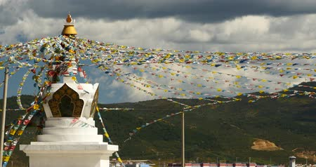 szerzetes : 4k buddhist white stupa & flying prayer flags with clouds background,shangrila yunnan,china. Stock mozgókép