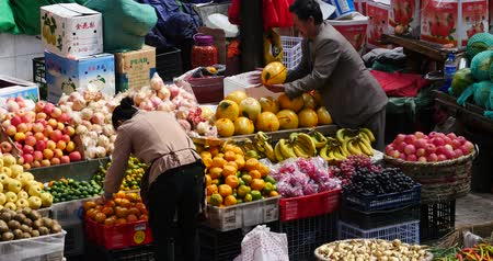 shangri la : 4k large outdoor fruits trade market in Shangri-La,china,minority women,variety of fruits in basket.