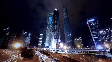 magas, szög, kilátás : time lapse,busy city traffic & brightly lit urban finance skyscraper at night,shanghai landmark building,huanqiu-building,shimao-building.Blue tone style,use Ultra-wide-angle lens shoot. Stock mozgókép