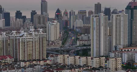 interseção : 4k urban busy traffic jams in dusk,QingDao,china.highway street & moder city business building.