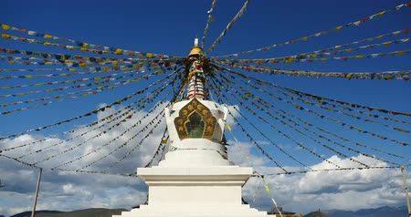 tanítvány : 4k buddhist white stupa and flying prayer flags with blue sky background,shangrila yunnan,china.