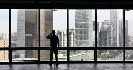marco internacional : 4k,businessman makes a phone call as overlooking the urban business building from window,skyscrapers,economic center. Stock Footage