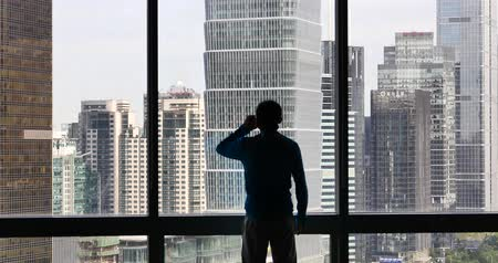 komerční : 4k,businessman makes a phone call as overlooking the urban business building from window,skyscrapers,economic center. Dostupné videozáznamy