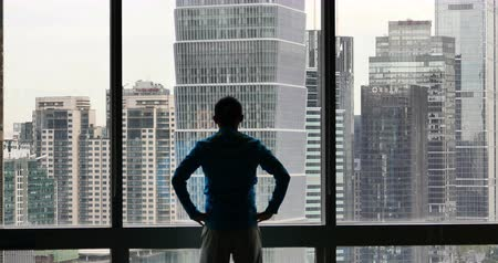 marco internacional : 4K, silhouette, businessman, back, raising, arm, Overlooking, the, victory, urban, building, from,, window, skyscrapers, economic, center Stock Footage