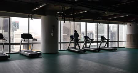 marco internacional : 4k,male running on cardio treadmills,urban business building,overpass traffic from window.