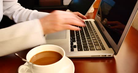 coffee press : 4k female sitting on the table,browing webpage on the laptop and ipad,keyboard input,hands typing on a computer keyboard,write article,writing report. Stock Footage