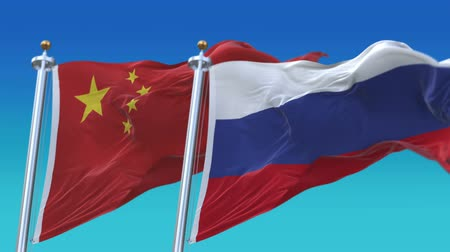 oy : 4k Russia and China Flags with blue sky background.