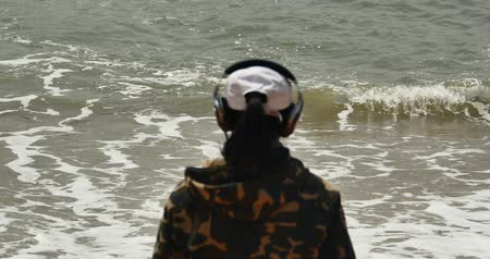 deep sea exploration : 4k Young man with earphones and facing the sea,enjoying the tunes in his headphones,wide ocean surface,waves washed sand,Big waves and surge.