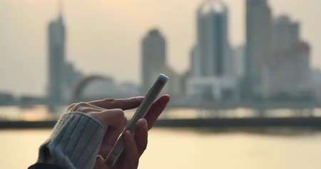 hallucinations : 4k people hand using a mobile phone against the vibrant and beautiful city coastline skyline,male using smartphone or cellphone to type a SMS or email against setting sunset.