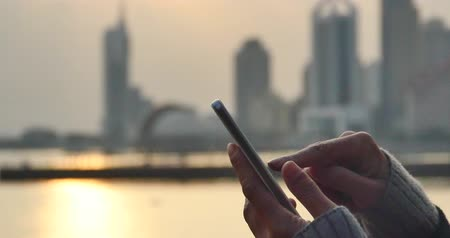 percepção : 4k people hand using a mobile phone against the vibrant and beautiful city coastline skyline. Stock Footage