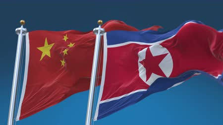 armed : 4k Seamless North Korea and China Flags with blue sky background, A fully digital rendering, The animation loops at 20 seconds Stock Footage