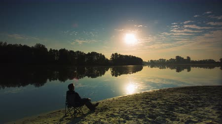 стулья : The man sit at the river (lake) bank. Early morning time. The very picturesque evaporation from water surface is seen. Time lapse. Shot with Red Dragon Cinema Camera and prime wide angle lens