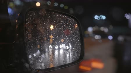 reflexão : The reflection of the rainy city in the right mirror of a car. Evening-night time, real time capture