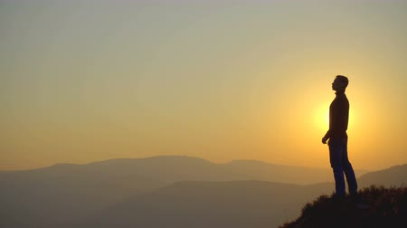 alpy : The man stand on the mountain on the background of sunset. Real time capture. Telephoto lens