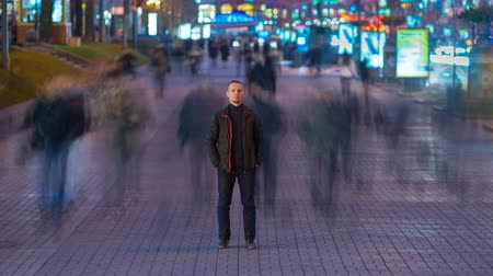 um : The man stand in the ghost-like crowd flow. Evening to night time. Time lapse Stock Footage