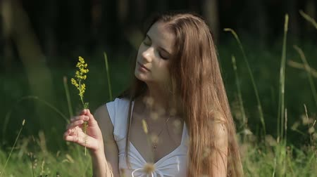 cheirando : Genuine woman in meadow sniffing flower.