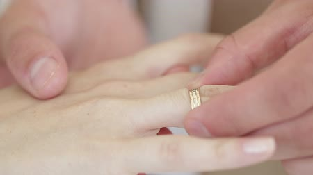 ring : man wears wedding ring on the hand of the woman