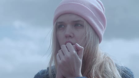 cold : Teenage girl warming hands with breathing Stock Footage