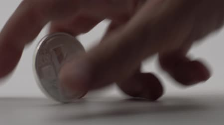 ele geçirmek : Slow motion of metal metallic Silver currency rolling on white background and one hand takes it. New worldwide virtual internet money. Digital coin in cyberspace, cryptocurrency LTC-Dan Stok Video