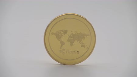 ellátó : 4K Physical metal golden Ripplecoin currency on white background. New worldwide virtual internet money. Digital Ripple coin cyberspace, cryptocurrency XRP. Good investment future online-Dan Stock mozgókép