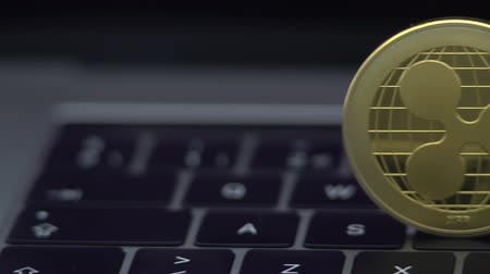 4K Physical metal golden Ripplecoin currency on notebook computer keyboard. Worldwide virtual internet money. Digital Ripple coin cyberspace, cryptocurrency XRP. Investment future online payment-Dan