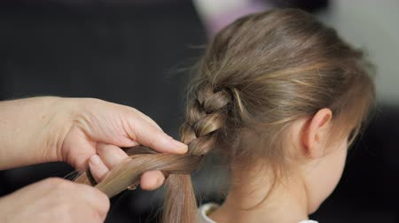 pigtailler : grandmother combs her granddaughters hair, braid the ponytail