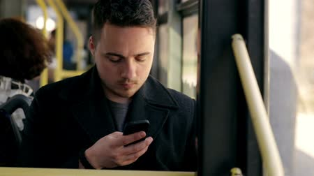 payment : Man in bus using his cell phone. Reading emails. texting  message