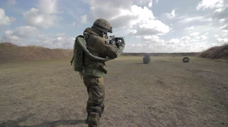 asker : A soldier with a machine gun on a military firing range shooting at a target. Stok Video